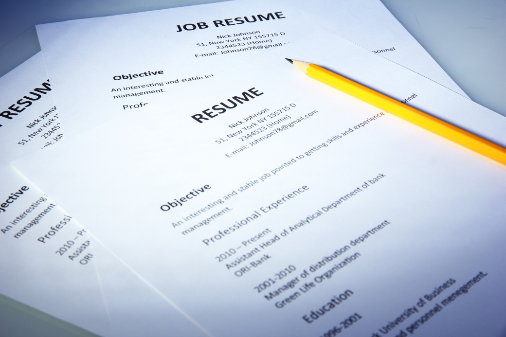Closeup of resume with pencil on blue background